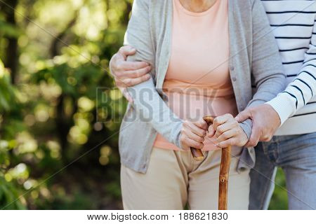 Fell my care . Caring loving senior man caring about his aged wife and helping her to make steps while hugging woman and walking in the park