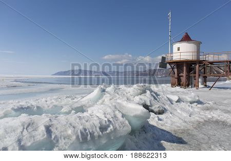 Transparent blue ice hummocks on lake Baikal shore. Siberia winter landscape view with lighthouse. Snow-covered ice of the lake. Big cracks in the ice floe