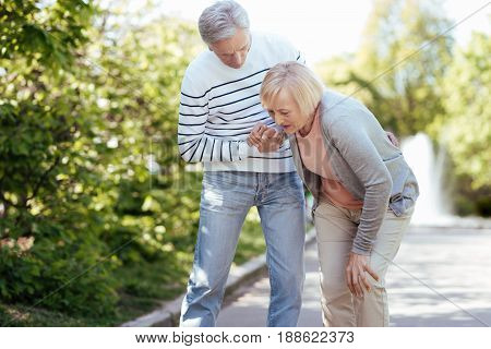 Difficultness of my senior age. Senior loving supportive man caring about his aging wife and helping her while strolling through the park