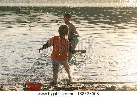 Children Bathe In The Evening On The City Beach