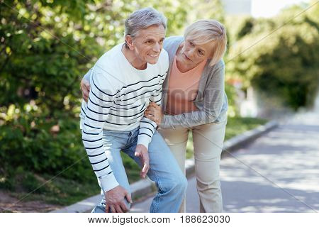 Need your help. Old confused panicked man suffering from ache in knee and expressing frustration while aged woman helping him outdoors