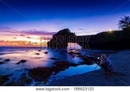 Professional Photographer With Camera And Tripod In Tanah Lot Temple At Sunset, Bali In Indonesia.(d