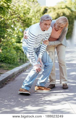 Sudden ache . Old charming helpful woman caring about husband and helping him to make step while walking in the park
