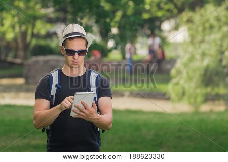 Backpacker finding location by using app on his digital tablet device. Vacation and travel concepts.