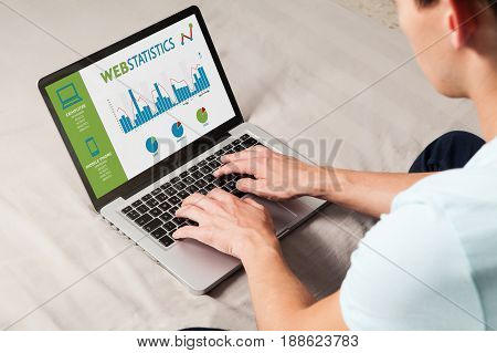 Man using a laptop computer for study web statistics information.