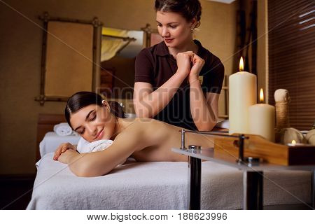 Masseur girl doing massage to woman in spa salon.
