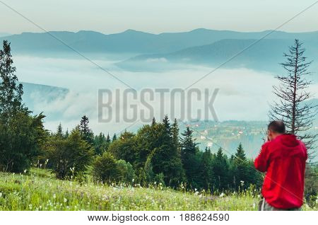 Photographer in the mountains. Guys in nature photograph forest environment, enjoying a beautiful spring afternoon. A man photographer takes pictures of the time in the mountains with a fog.