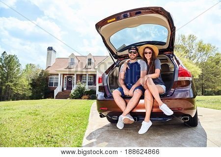 Couple, Men And Woman Sitting In Cars Trunk And Smiling