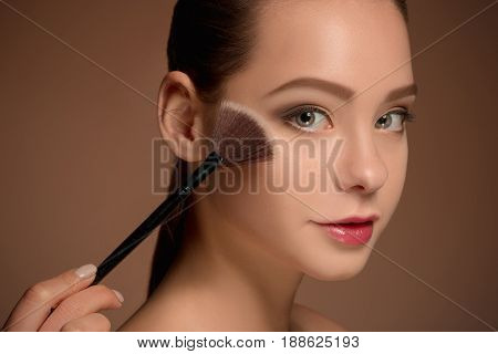 Beauty Girl with Makeup Brush. Bright Make-up for Brunette Woman with Beautiful Face. Perfect Skin. Applying Makeup