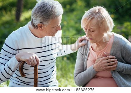 What is wrong with you. Concentrated motionless senior woman touching her chest and having heart attack while her husband worrying about her and sitting on the bench outdoors