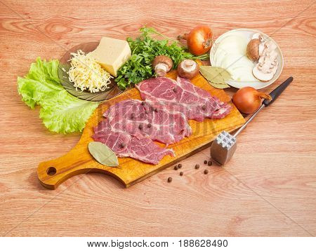 Sliced uncooked pork neck on the wooden cutting board cheese mushrooms onion greens and spices for cooking french-style meat beside meat tenderizer on a wooden surface