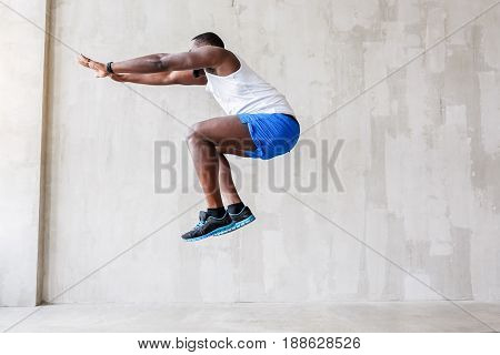 Take spring. Excited bearded african man is getting stuck in the air showing fragment of leap. He is reaching out his arms forward and bending his knees