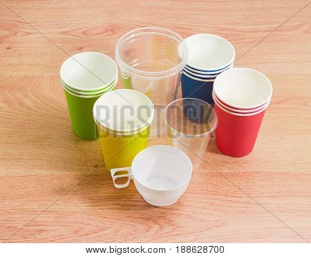 Different disposable transparent and white plastic cups piles of the disposable paper cups in red green blue and yellow colors on a wooden surface