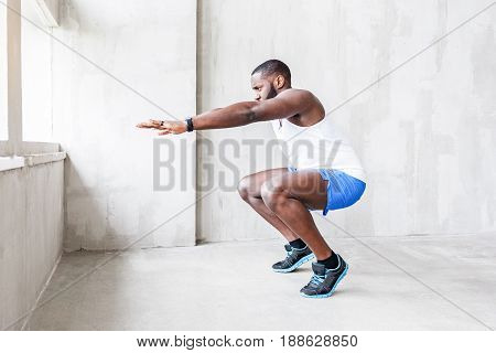 Strong african bearded athlete is doing knee bends. Serious muscular guy is looking straight while making exercise