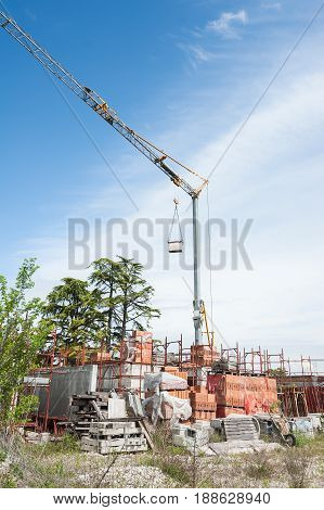 Small construction site with houses under construction. Construction cranes scaffolding bricks and other building materials.