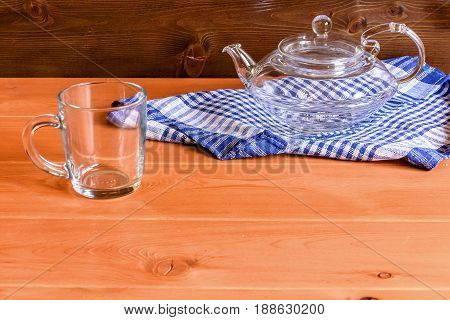 Glass teapot stands on a blue towel on a wooden background.