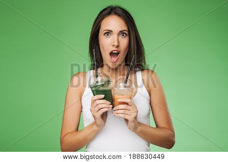 Young attractive brunette woman holding takeaway cup of smoothie. Happy girl posing on green background. Healthy eating concept.