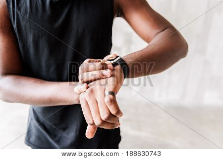 It is time. Serious african athlete is checking exercise time. Close up of sportsman hand watch.