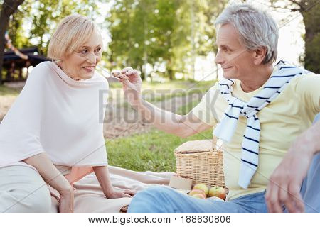 In a delightful mood . Optimistic loving retired couple expressing love while enjoying picnic outdoors and feeding each other