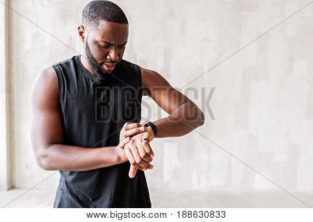 Worried young bearded sportsman is looking at his hand watch. Copy space in right side