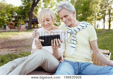 Getting acquainted with new gadget. Positive joyful senior couple expressing happiness while enjoying picnic outdoors and using electronic gadget