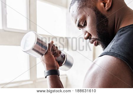 Serious looking athlete with beard is straining his biceps using dumbbell. He is concentrated on exercise