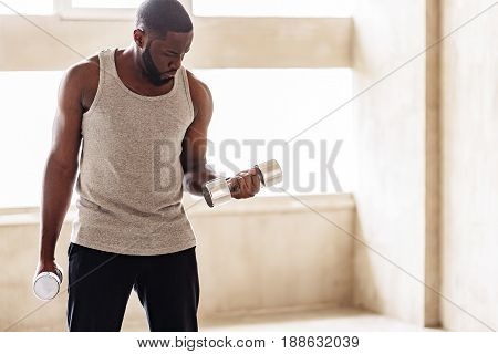 Stern attractive well-build man is lifting hands with dumbbells one by one. Copy space in right side