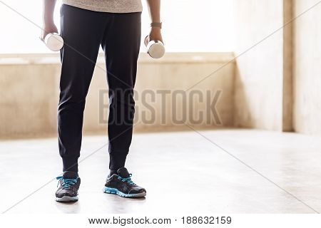 Quiet athlete is standing straight holding hand weights in both arms. Close up of muscular guy legs