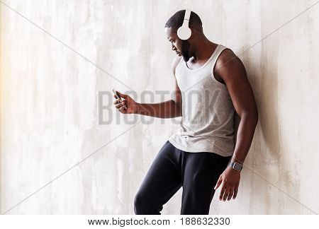 Somber young athlete is leaning on wall and listening to music. He is holding player and using headphone. Copy space in left side