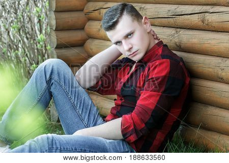 Young man wearing red checked shirt and blue jeans outdoor portrait