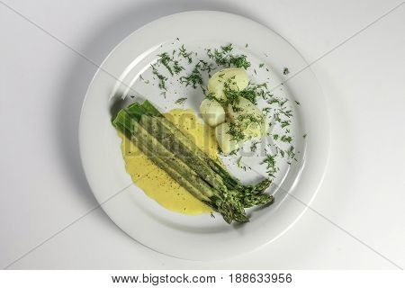 Bunch of cooked asparagus on white plate with hollandaise sauce potatoes and dill on a white background isolated. Horizontal viem