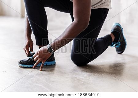 Close up of legs of african sportsman putting on sneakers. He is preparing for exercise. Focus on smart watch on his wrist and ring on little finger