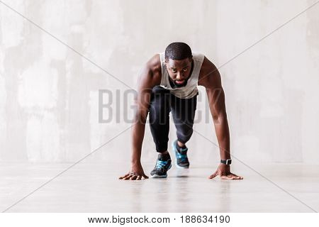 Portrait of serious bearded african athlete. He is standing in crouch start pose. Focus on hand watch on his wrist
