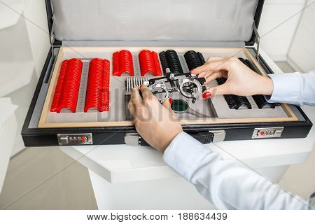 optometrists hand open suitcase with set of trial lenses in ophthalmology clinic.