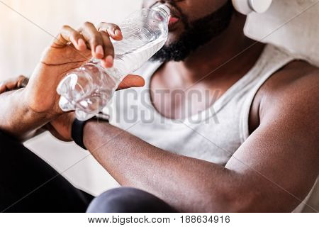 Close up of hands of young bearded athlete holding bottle of water. He is sitting on floor, leaning on wall and drinking