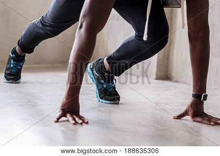 Close up of hands and legs of african well-build sportsman standing in crouch start pose. Focus on smart watch and training shoes