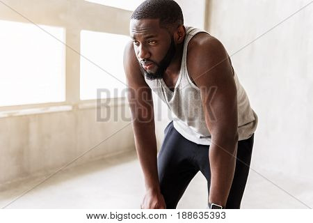 Portrait of tired young bearded sportsman finishing training activity. He is standing on half bent legs and looking far away