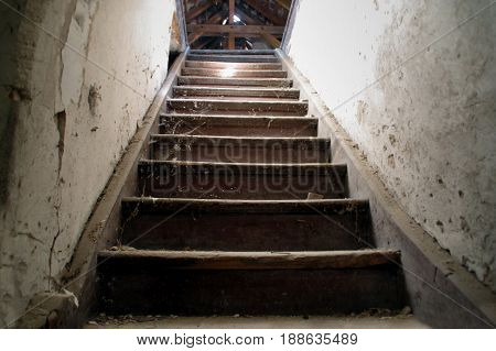 Old damaged wooden stairs to the garret. Entrance to the attic.
