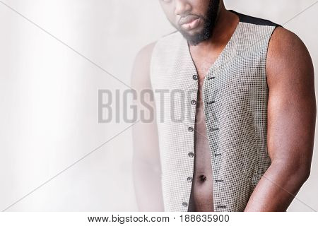 Close up of stylish waistcoat of handsome bearded african man. He is wearing it on nude body. Copy space in left side