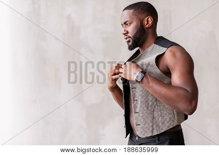 Serious young sexy muscular man with beard is demonstrating fashionable suit. Focus on smart watch and modern waistcoat. Copy space in left side