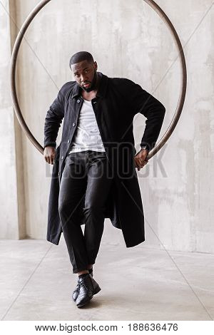 Full length portrait of serious african bearded guy wearing stylish long black coat. He is sitting on big metal ring hanged on ceiling