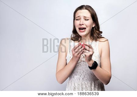 Portrait of sick cold woman with freckles and white dress and smart watch on silver gray background. healthcare and medicine concept.