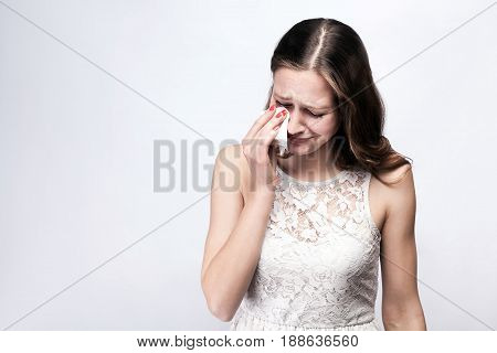 Portrait of sad, unhappy crying woman with freckles and white dress and smart watch on silver gray background. copy space. healthcare and medicine concept.
