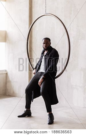 Portrait of self-assured trendy handsome african man with smart watch on his wrist. He is leaning on huge metal ring and wearing long black coat and leather shoes. Vogue concept