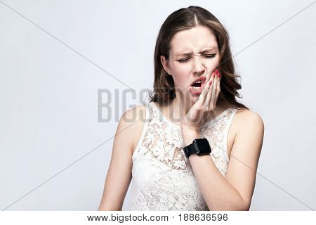 Portrait of beautiful woman with freckles and white dress and smart watch with tooth pain on silver gray background. healthcare and medicine concept.