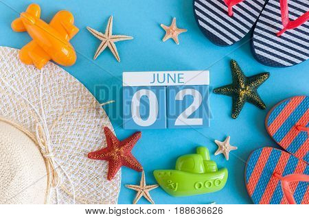 June 2nd. Image of june 2 calendar on blue background with summer beach, traveler outfit and accessories. Summertime concept.