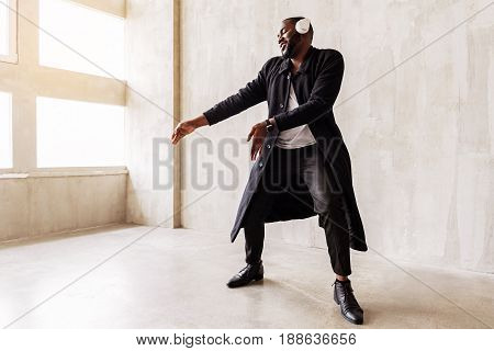 Joyful handsome man with beard is wearing long black coat, stylish trousers and leather shoes. He is dancing while listening to music. Vogue concept