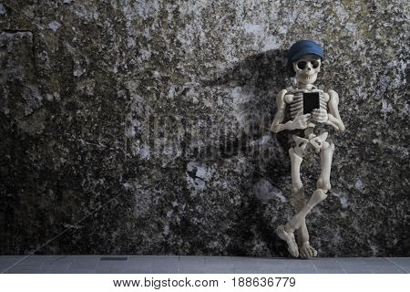 A skeleton leaning on a grungy wall with smartphone in his hand
