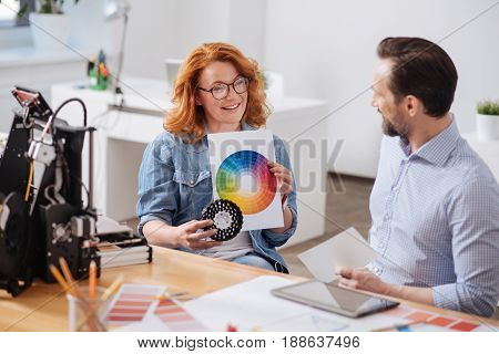 Choosing the colour. Delighted nice positive woman holding a colour palette and showing it to him while choosing the colour together