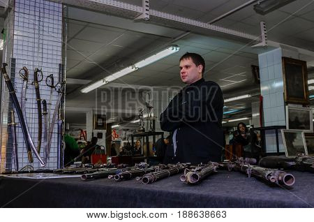 Moscow, Russia - March 19, 2017: Old antique guns, rifles for sale on the collectors market. Selective focus on rifle muzzle, man in black aand a panorama of flea market in the background